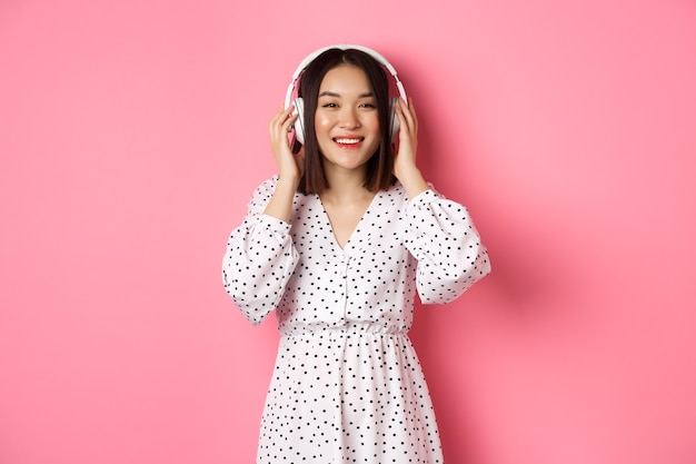 Романтичная азиатская женщина улыбается счастливой, слушает музыку в наушниках и смотрит в камеру, стоя на розовом фоне