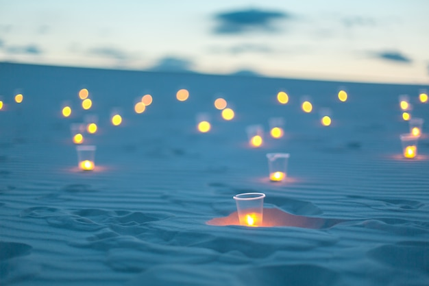 Romantic atmosphere lighting candles in sand desert