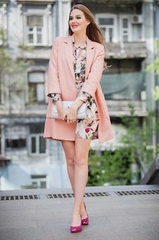 ピンクのコートで街を歩くロマンチックな魅力的なスタイリッシュな笑顔の女性