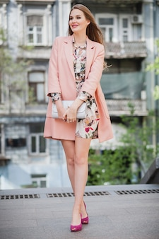 Romantic attractive stylish smiling woman walking city street in pink coat