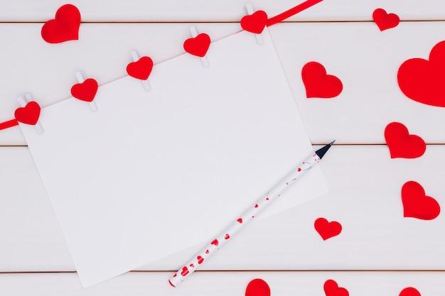 Романтический фон. лист бумаги, украшенный красными шелковыми сердечками на белом деревянном фоне.