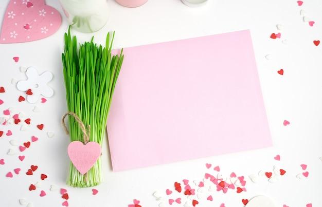 明るい背景にハート、ピンクの封筒、緑の花束とピンクの色調のロマンチックな背景。コピーするスペースのある上面図。バレンタインデーのコンセプト。