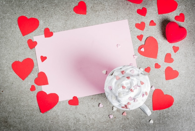 Romantic background valentine's day stone table with blank paper for letter congratulations hot chocolate with whipped cream and sweet hearts decorated with paper red hearts