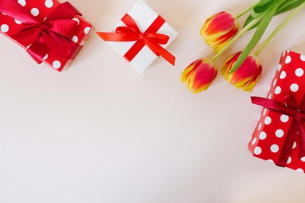 光の上のチューリップとギフトボックスの花束とロマンチックな背景。コピースペースのある上面図。バレンタインデーの背景。