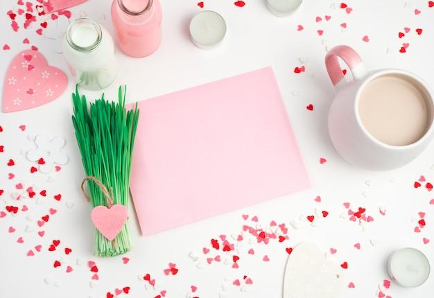 ハート、コーヒーカップ、ピンクの封筒、明るい背景の草の束とロマンチックな背景。コピーするスペースのある上面図。ピンクの色調で。 2月14日のコンセプト、女性の日。