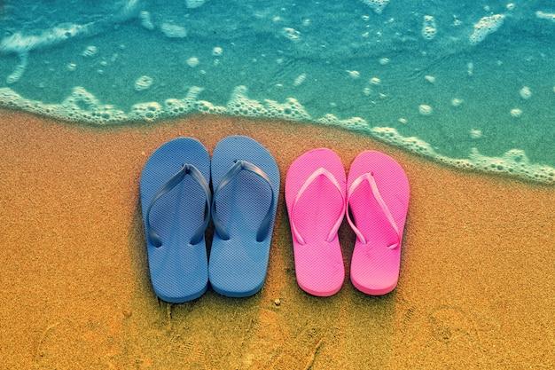 ロマンチックなビーチシーン。ビーチで女性と男性のフリップflppサンダル