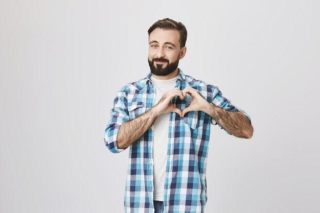 Romantic bearded man showing heart sign, express love