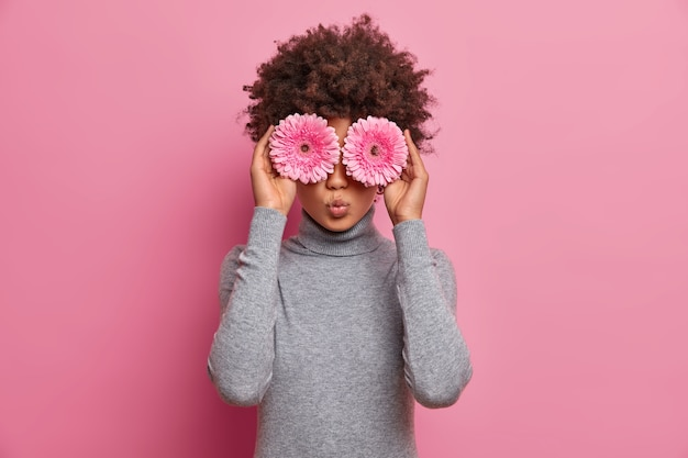 Romantic beautiful curly haired woman keeps pink gerberas over eyes, has spring mood, dressed in casual grey turtleneck, going to make bouquet from flowers