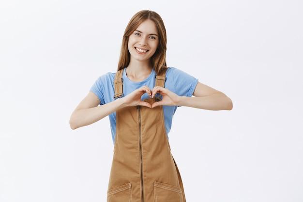 Романтичная красивая девушка показывает жест сердца и улыбается