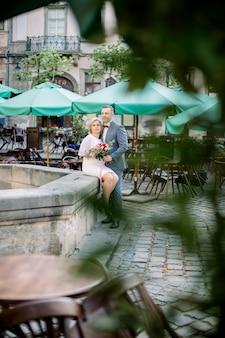 분수 옆 도시 광장에 서 있는 낭만적인 아름다운 중년 부부