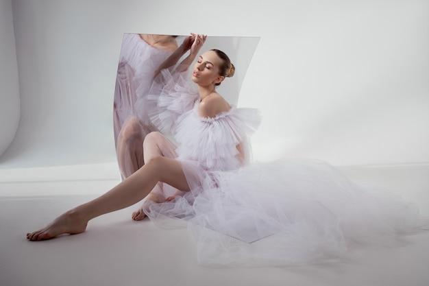 Романтичная красивая женщина в легком платье отражается в зеркале