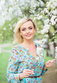 Romantic beautiful woman in a park on the lake stands against a flowering tree. beautiful woman in a floral dress