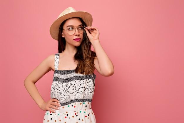 ロマンチックな美しい若い女性は夏の帽子とメガネのポーズで明るいドレスを着てください。