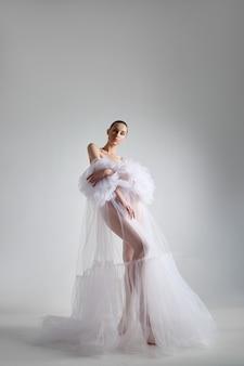Романтическая красавица женщина в легком платье стоит на белом фоне, длинные ноги. натуральная косметика, красивая гладкая кожа лица, пучок волос