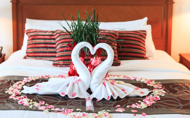 Romantic bedroom interior, kissing swan origami towels and sprinkled fresh pink white rose