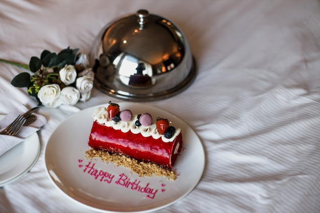 Romantic birthday cake with white rose on the bed