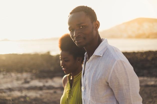 Романтическая черная раса счастливая пара в любви африканских молодых людей гуляет вместе с океаном и пляжем, наслаждаясь активным отдыхом на свежем воздухе вместе. красивый портрет мужчины и женщины