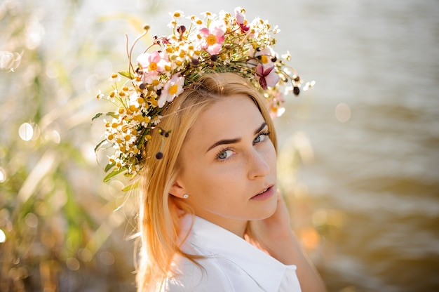Romantic blond girl in a wreath of flowers