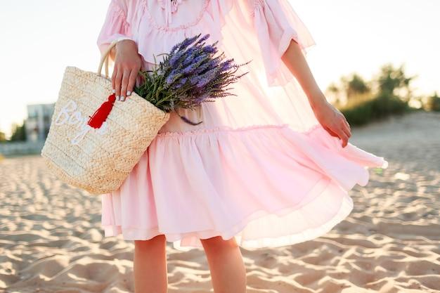 귀여운 핑크 드레스 춤과 해변에서 푸 데 로맨틱 금발 여성. 밀짚 가방과 라벤더 꽃다발을 들고. 자유와 자연 개념.