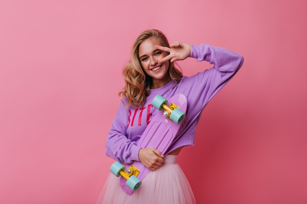 Романтичная блондинка позирует со знаком мира на розовом. очаровательная кудрявая женщина держит розовый скейтборд и смеется.