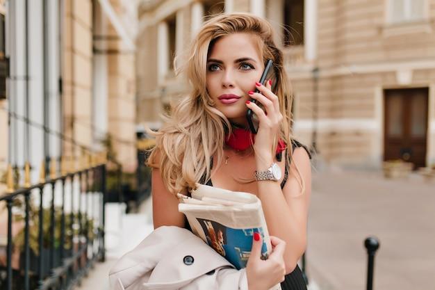 一緒に時間を過ごすために彼女を招待する友人を呼び出すロマンチックなブロンドの女性