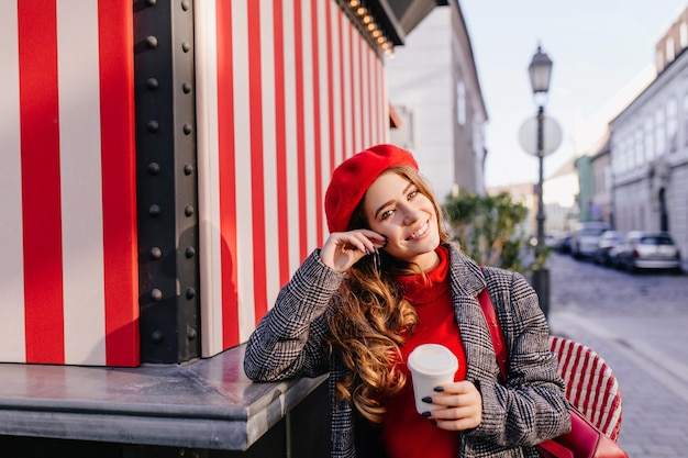 Романтичная голубоглазая женщина в берете мечтательно позирует с чашкой кофе