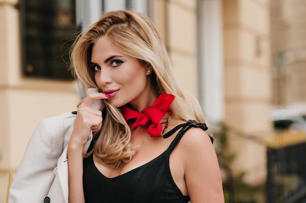 Romantica donna dagli occhi azzurri con la pelle abbronzata trascorrere del tempo in città esplorando nuovi posti