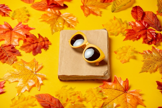 Romantic book and sunglasses with autumn leaves on yellow background. top view