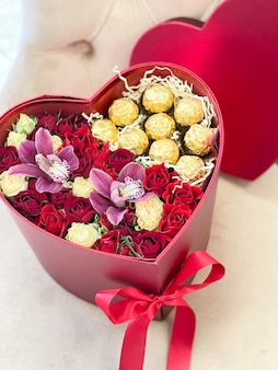 Romantic bouquet of flowers in a red heart box with roses, orchids and chocolates for a holiday gift