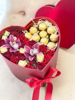 Романтический букет цветов в красной коробке-сердечке с розами, орхидеями и шоколадными конфетами в подарок к празднику.