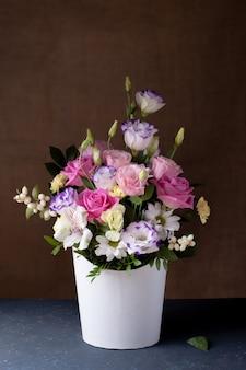 Романтический букет из роз, ромашек, лизиантусов, хризантем, неоткрытых бутонов в белой круглой коробке.