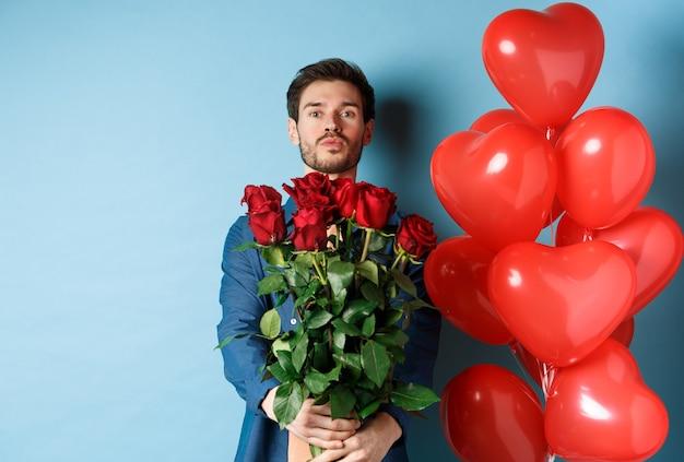 로맨틱 한 남자 친구 사랑에 고백하고 장미 꽃다발, 키스를위한 주름 입술, 파란색 배경에 하트 풍선과 함께 서.