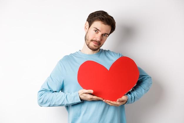 Fidanzato romantico che fa una sorpresa per san valentino, tiene in mano un grande ritaglio di cuore rosso sul petto e sorride con amore, guardando tenero la telecamera, in piedi su sfondo bianco