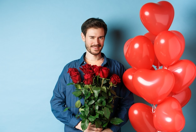 낭만적 인 남자 친구 윙크 하 고 웃 고, 발렌타인 데이에 꽃의 꽃다발을 들고, 연인, 파란색 배경에 대 한 심장 풍선 근처에 서.