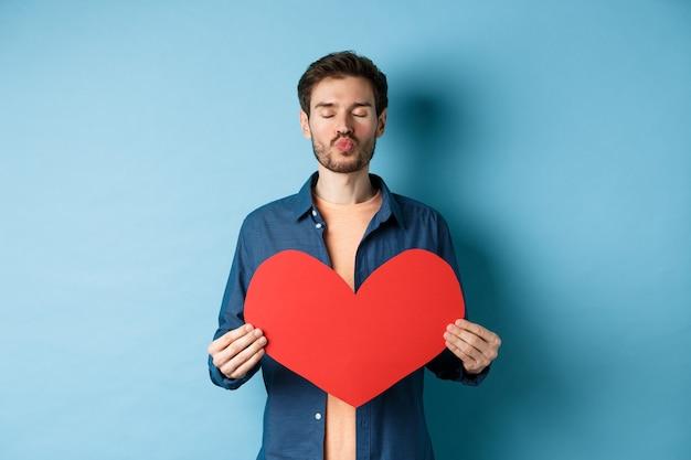 バレンタインの赤いハートのロマンチックなボーイフレンドは目を閉じ、唇をパッカーし、青い背景に立って、恋人の日にキスを待っています。