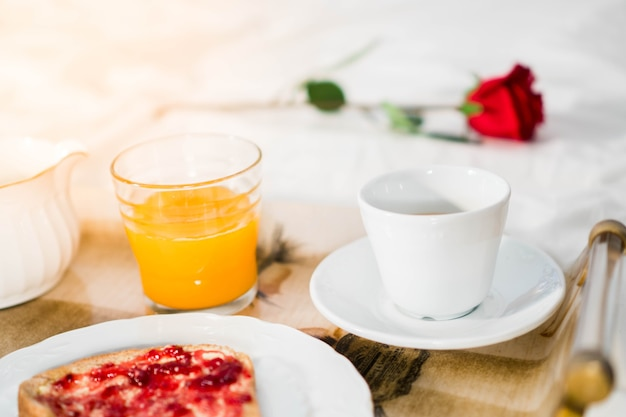 Romantic breakfast in bed with orange juice, coffee and toast with jam and a red rose.