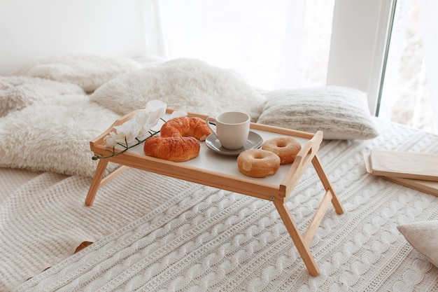 Romantic breakfast in bed on a wooden tray with croissants, donuts and orchid flowers