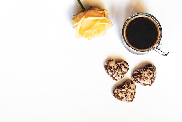 Romantic breakfast, coffee, chocolate cakes in the shape of hearts and a yellow rose on a white background, flat lay copy space