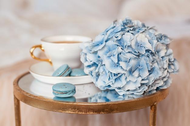 寝室の背景にお茶のマカロンと青いアジサイの花のロマンチックな朝食カップ