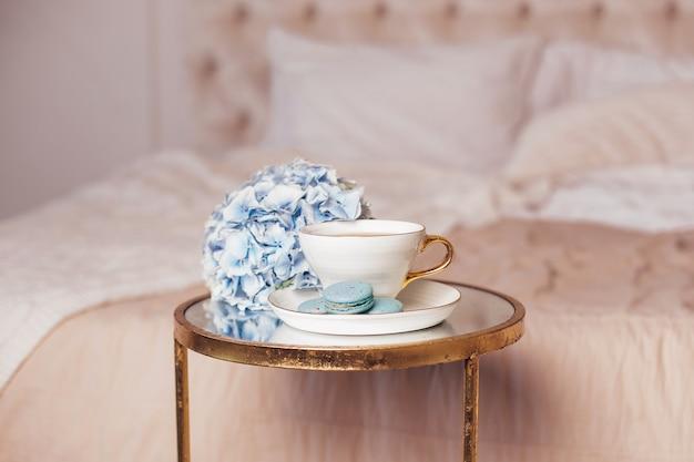 Romantic breakfast cup of tea macaroons and blue hydrangea flower on bedroom background