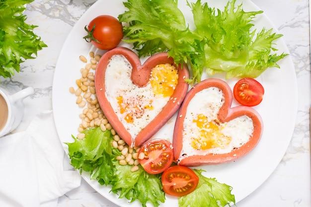 Романтический завтрак. жареные яйца в сосисках в форме сердца, листья салата и помидоры черри на тарелке на столе. вид сверху. крупный план