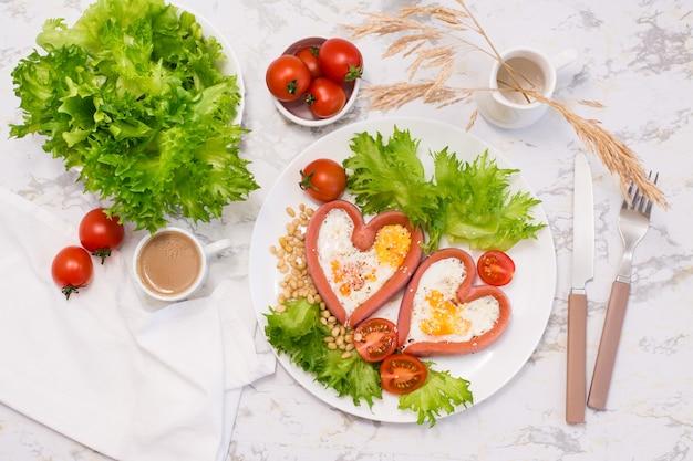 Романтический завтрак. жареные яйца в сосисках в форме сердца, листья салата и помидоры черри на тарелке на столе. вид сверху