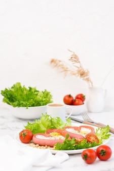 Романтический завтрак. жареные яйца в сосисках в форме сердца, листья салата и помидоры черри на тарелке на столе. вертикальный вид. копировать пространство