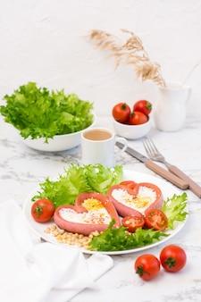 Романтический завтрак. жареные яйца в сосисках в форме сердца, листья салата и помидоры черри на тарелке на столе. вертикальный вид
