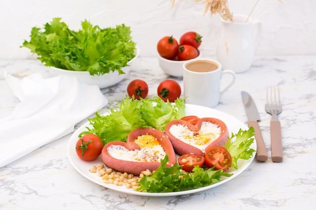 Романтический завтрак. жареные яйца в сосисках в форме сердца, листья салата и помидоры черри на тарелке на столе
