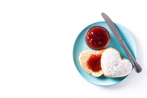 Romantic breakfast, heart-shaped bun and berry jam on white surface