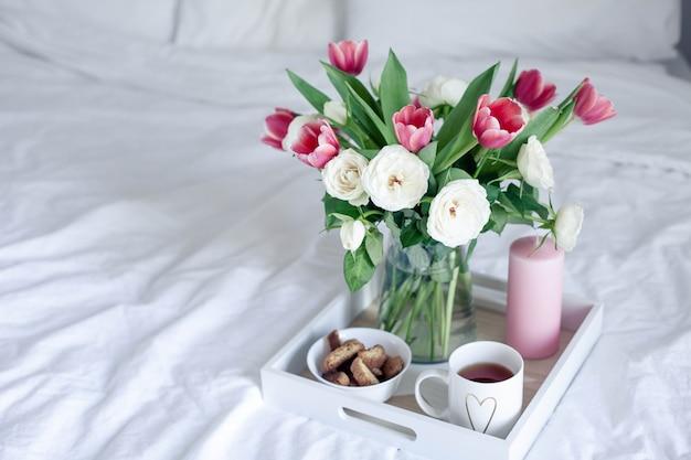 ベッドでのロマンチックな朝食。花の花束。バラとチューリップ。