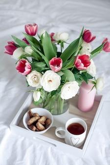 침대에서 낭만적 인 아침 식사. 꽃의 꽃다발. 장미와 튤립.