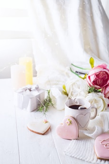 Романтический завтрак в постель. кофе, печенье, подарочная коробка и цветок на деревянный стол. день святого валентина