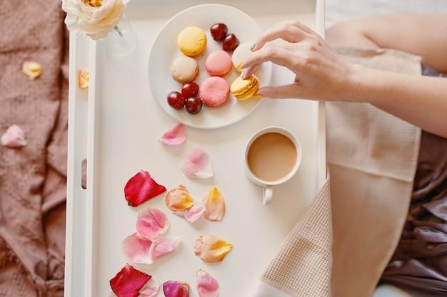 マカロンの香りのよいコーヒーを持っている女性の手のバレンタインデーの上面図のためのベッドでのロマンチックな朝食...